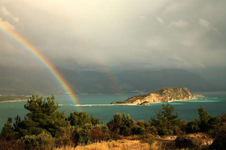 Magic moment after storm – view from hills near Budva – Montenegro. Rainbow above small bay.