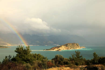 Magic moment after storm � view from hills near Budva � Montenegro. Rainbow above small bay. photo