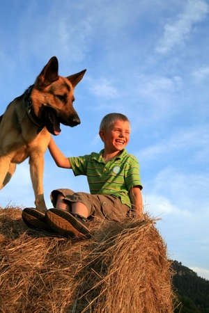 Little boy playing with the dog (Alsatian) on the meadow - summer in the Stolowe Mountains, Pasterka, Poland