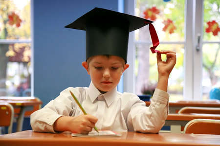 The young student, first-form pupil,  sitting in the school bench in the student cap, biretta. Start of the school year, classroom. Schoolboy. Stock Photo