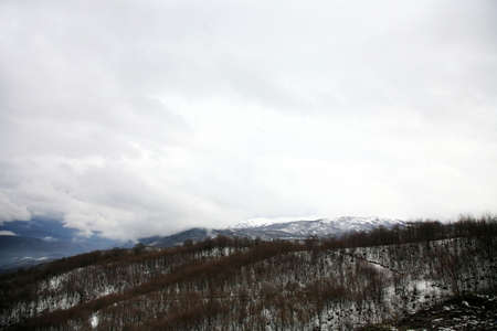 Low gliding clouds above peaks of the Balkans, cloudy day high in the mountains, Macedonia. photo