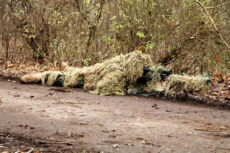 concealed: Soldiers game on military training ground ( batlle camp ). Soldier in camouflage, lies ready for the shot