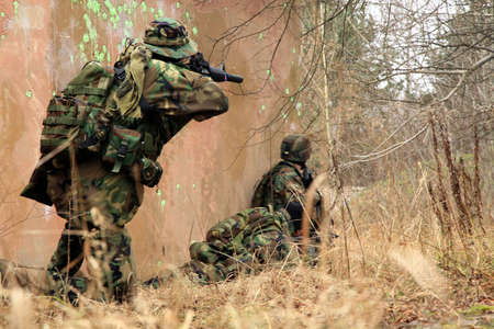 Soldiers in camouflage game on military training ground ( batlle camp ).