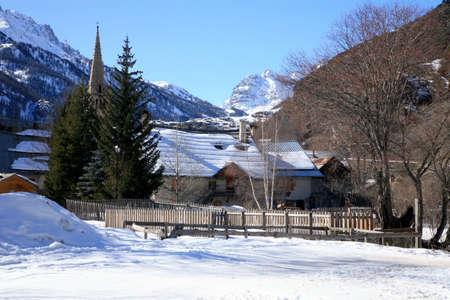 Clouds over the valley de la Claree. Nevache – small village in French Alps. House in snow - winter scenery.  photo