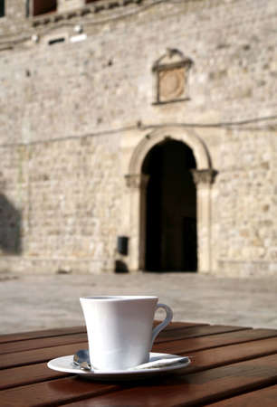 One, white, cup of coffee on table in old harbor in Dubrovnik – Stari Grad. In background-  the gate and curtain walls of the Old Town. photo