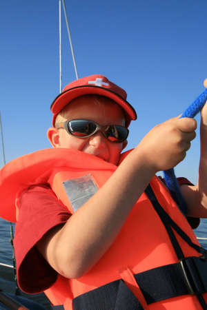 Boy in the life jacket with sunglasses on the yacht. He is pulling sheets (ropes). Work aboard, sailing. 版權商用圖片 - 4417471