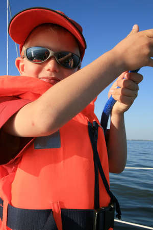 Boy in the life jacket with sunglasses on the yacht. He is pulling sheets (ropes). Work aboard, sailing. photo