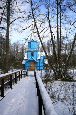 Picturesque blue Orthodox Church on a forest clearing, covered with the snow. Winter scenery. Important place of worship in small village Koterka, east part of Poland.  photo