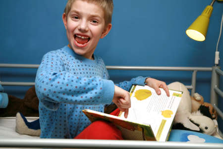 bedside: Young boy sitting in the bed with pajamas and reading book about plants. Evening in the child room. Stock Photo