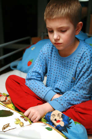 Young boy sitting in the bed with pajamas and reading book about plants. Evening in the child room. photo