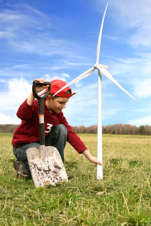 Happy little boy with small windmill and spade. He is planting small windmills on green meadow by spring