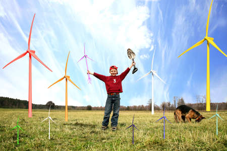Smiling happy little boy with small windmill and spade. He is planting small windmills on green meadow by spring with his dog.