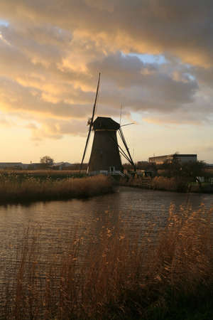 Traditional Dutch pumps by sunset - old windmills in Kinderdijk, Netherlands. In 1997 these windmills were put on the World Heritage List of UNESCO. photo