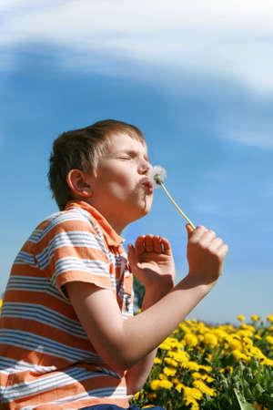 herbage: Little boy is blowing dandelion on meadow full of yellow dandelions by may.