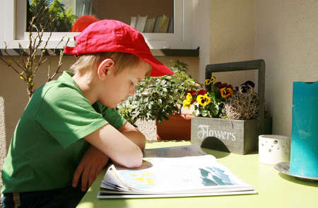 Young boy sitting on the balcony and reading book about geographic. Sunny day by spring in city.