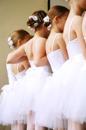 performance art: Little ballerinas dancing on a school show. Schoolgirls dressed in white dresses ( tutu ) with a daisy in their hair.