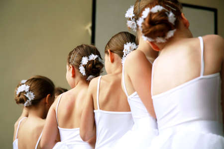 Little ballerinas dancing on a school show. Schoolgirls dressed in white dresses ( tutu ) with a daisy in their hair. Stock Photo - 4954950