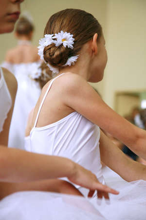 Little ballerinas dancing on a school show. Schoolgirls dressed in white dresses ( tutu ) with a daisy in their hair. Stock Photo - 4954952
