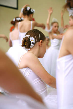 Little ballerinas dancing on a school show. Schoolgirls dressed in white dresses ( tutu ) with a daisy in their hair.