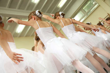 Little ballerinas dancing on a school show. Schoolgirls dressed in white dresses ( tutu ) with a daisy in their hair. photo