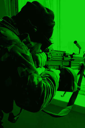 night vision: Military training ground ( batlle camp ) in Poland. Soldiers during night exercises - conducting the attack inside the building at night. View through the night vision device. Stock Photo