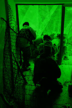 Military training ground ( batlle camp ) in Poland. Soldiers during night exercises - conducting the attack inside the building at night. View through the night vision device. photo