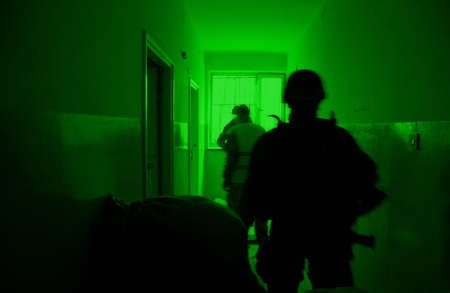 Military training ground ( batlle camp ) in Poland. Soldiers during night exercises - conducting the attack inside the building at night. View through the night vision device. Stock Photo