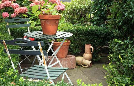 Malerischen kleinen Garten in Seitenstraße in den Niederlanden mit Hortensien, Krüge, Tisch und Stühlen und Absicherung.