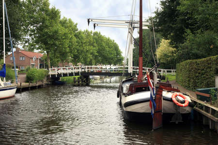 bowsprit: View on typical canal with different boats and white drawbridge. Blokzijl, Netherlands.