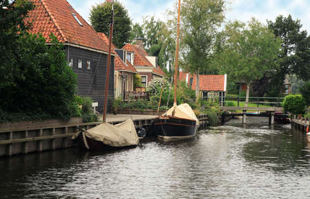 View on typical canal with different boats and white drawbridge. Blokzijl, Netherlands.