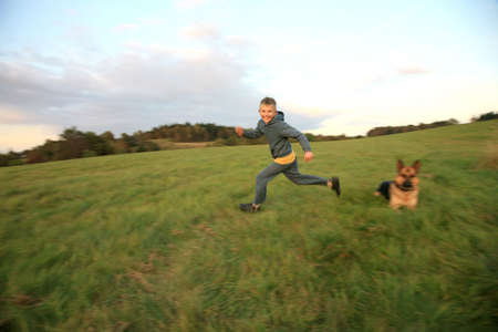 Happy, little boy running on the green, mountain meadow at sunset with his faithful a large dog - German Shepherd.