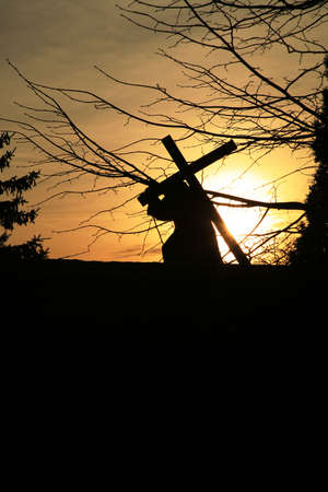 Figure of the Jesus carrying the cross. View of the silhouette at sunset . Empty space for text. Standard-Bild