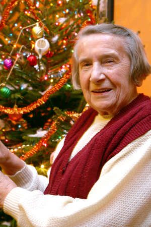 Grandmother is sitting by the festive Christmas tree. Christmas time.  photo