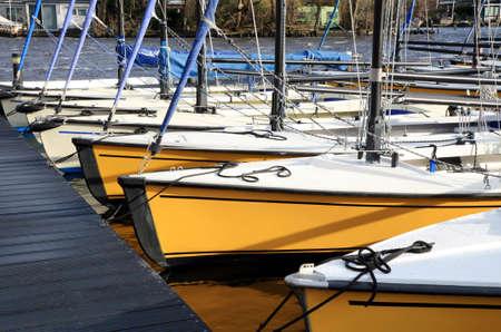 Kleine, Freizeit-festgemachten Segelboote in der Marina warten bereit auf die Segeln-Saison zu beginnen. Niederlande. Standard-Bild