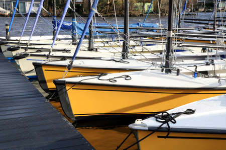 Small, recreational moored sailing boats in the marina are waiting ready to begin the sailing season. Netherlands.