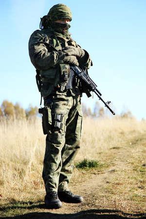Bewaffneter Soldat in Camouflage ruht sich nach der Patrouille.