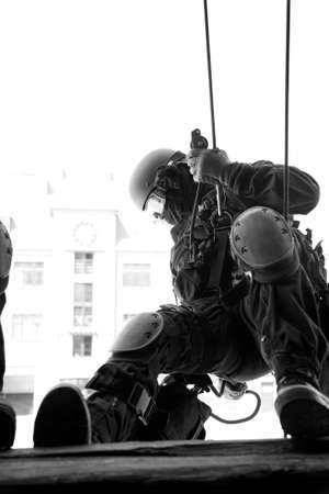 Subdivision anti-terrorist police during a black tactical exercises. Rope Techniques.