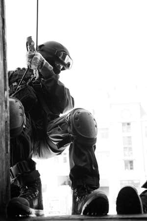 terrorists: Subdivision anti-terrorist police during a black tactical exercises. Rope Techniques.  Real situation. Black and white photo with film grain.