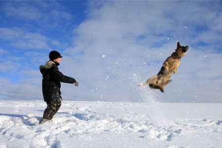 Teenage boy playing with dog in winter, sunny day on a meadow covered with snow. Stock Photo