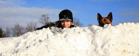 Teenage Junge spielt mit Hund im Winter, sonnigen Tag auf einer Wiese mit Schnee bedeckt.