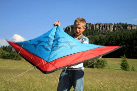 Teenage, Caucasian boy made kite on a mountain meadow - Table Mountains in Poland in village Pasterka photo