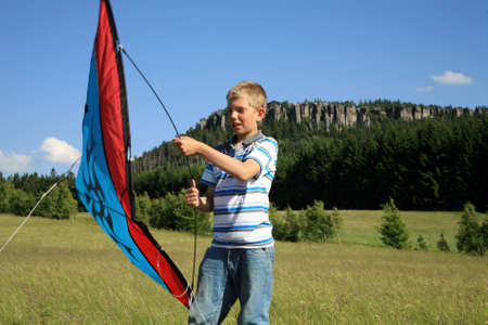 Teenage, Caucasian boy made kite on a mountain meadow - Table Mountains in Poland in village Pasterka photo