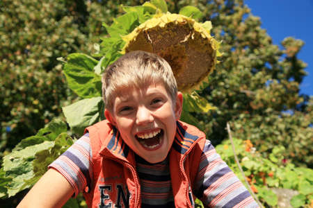 Funny blond teenage boy under sunflower   Autumn in the garden  Seasonal plants  photo