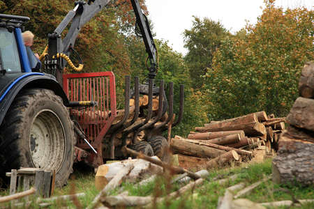 logging truck: Unloading firewood  Winter fuel supplies to villages in the mountains  Autumn works  Stock Photo