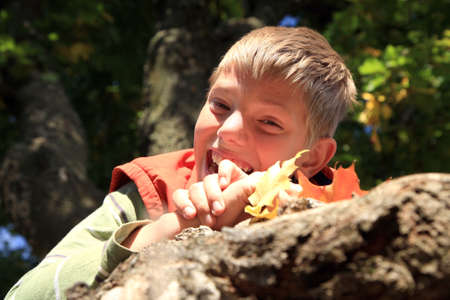 Funny blond teenage boy under tree with colored leaves   Gold autumn Seasonal colors  photo