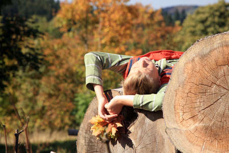 Blond boy sunbathing on wooden balls  Warm, golden autumn  Beautiful weather  photo