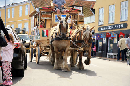 hitched: Svaneke,  Denmark – August 15, 2012  Old horse tram takes tourists on the streets of the city  Touristic attraction  in Svaneke in Denmark