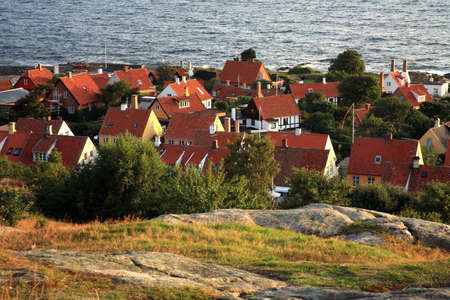 Panorama of picturesque small town Gudhjem with red roofs by early morning, Bornholm, Denmark photo