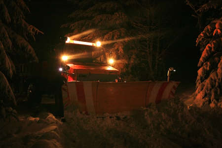 tree removal service: Night snow plow during maintenance road in winter  Country road on mountains  Photo with the noise and grain characteristic of night photographs