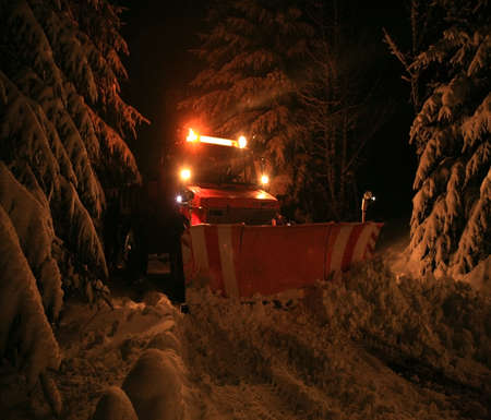drifting ice: Night snow plow during maintenance road in winter  Country road on mountains  Photo with the noise and grain characteristic of night photographs